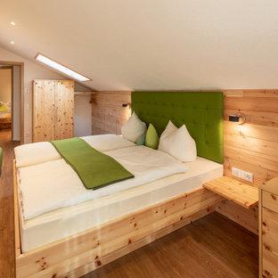Mittelgroßes Landhaus Hauptschlafzimmer mit weißer Wandfarbe, braunem Holzboden und braunem Boden in Sonstige