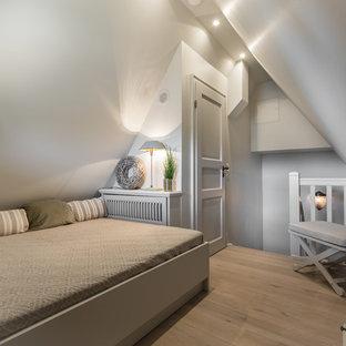Foto di una piccola camera da letto country con pavimento in legno massello medio, nessun camino e pareti grigie