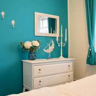 Diseño de habitación de invitados actual, pequeña, sin chimenea, con paredes azules, suelo de baldosas de cerámica y suelo negro