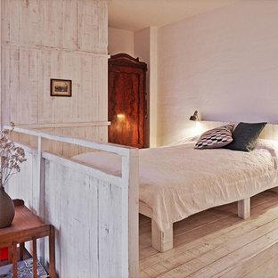 Mittelgroßes Skandinavisches Schlafzimmer im Loft-Style, ohne Kamin mit weißer Wandfarbe, hellem Holzboden und beigem Boden in Berlin