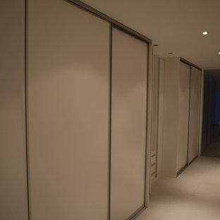 Esempio di una piccola camera matrimoniale minimal con pareti bianche, moquette, camino bifacciale e pavimento bianco