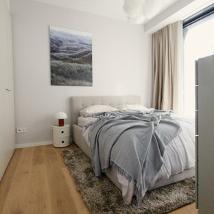 Modernes Schlafzimmer mit grauer Wandfarbe, braunem Holzboden und braunem Boden in Frankfurt am Main