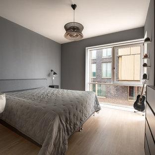 Mittelgroßes Skandinavisches Hauptschlafzimmer mit grauer Wandfarbe und braunem Holzboden in Hamburg