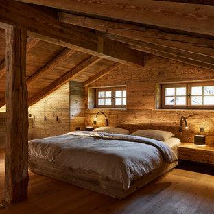 Großes Uriges Hauptschlafzimmer ohne Kamin mit brauner Wandfarbe, gebeiztem Holzboden und braunem Boden in München