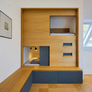Inspiration for a small contemporary guest bedroom in Other with white walls, medium hardwood flooring and no fireplace.