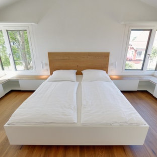 Inspiration for a small scandinavian master medium tone wood floor bedroom remodel in Other with white walls and no fireplace