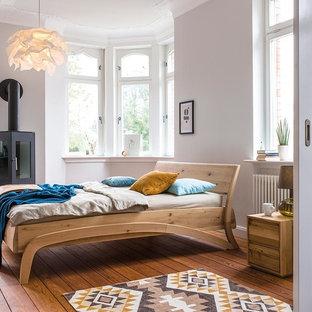 Imagen de dormitorio principal, nórdico, de tamaño medio, con paredes blancas, suelo de madera pintada, estufa de leña y marco de chimenea de metal