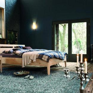 Imagen de dormitorio principal, campestre, grande, con paredes azules, suelo de madera pintada y estufa de leña