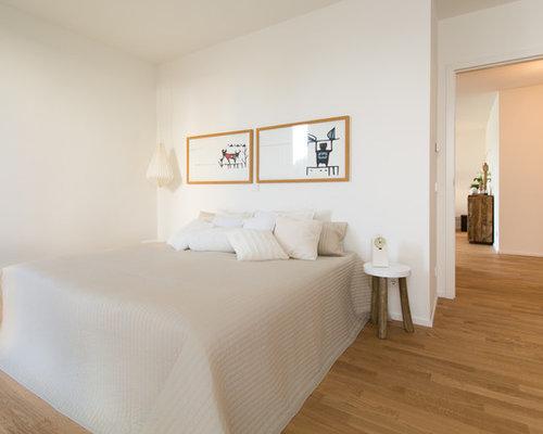 Mid Sized Scandinavian Master Medium Tone Wood Floor Bedroom Idea In Essen  With White Walls
