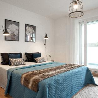 Modernes Schlafzimmer mit weißer Wandfarbe, braunem Holzboden und braunem Boden in Köln