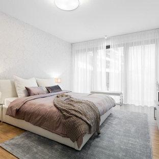 Mittelgroßes Modernes Hauptschlafzimmer mit weißer Wandfarbe, braunem Holzboden und braunem Boden in Berlin