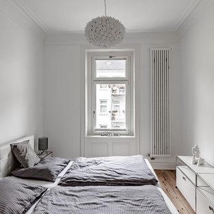 Nordisches Schlafzimmer mit weißer Wandfarbe, braunem Holzboden und braunem Boden in Hamburg