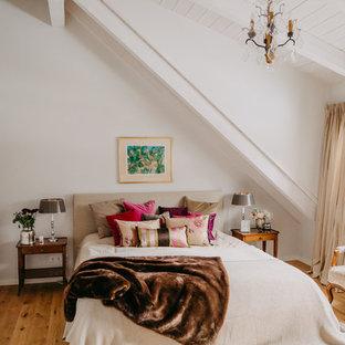 Klassisches Schlafzimmer mit weißer Wandfarbe, braunem Holzboden und braunem Boden in München