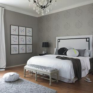 Cette photo montre une chambre parentale éclectique de taille moyenne avec un mur gris, un sol en bois brun et aucune cheminée.