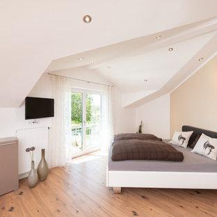 Großes Modernes Hauptschlafzimmer ohne Kamin mit weißer Wandfarbe, braunem Holzboden und beigem Boden in Nürnberg