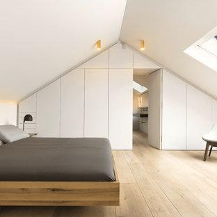 Imagen de dormitorio principal, contemporáneo, grande, sin chimenea, con paredes blancas y suelo de madera clara