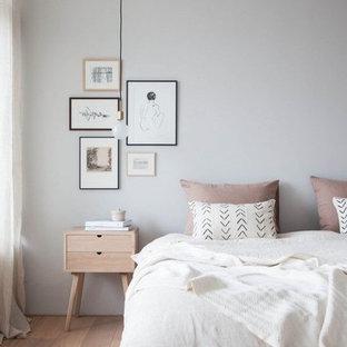 Ispirazione per una piccola camera matrimoniale scandinava con pareti grigie, pavimento in legno massello medio, nessun camino e pavimento marrone