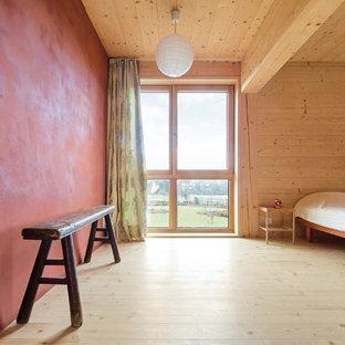 Cette photo montre une très grand chambre parentale nature avec un mur rouge, un sol en bois clair et un sol beige.