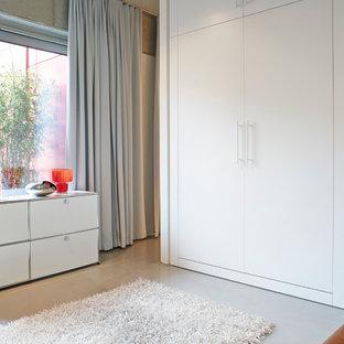 Geräumiges Industrial Schlafzimmer im Loft-Style mit grauer Wandfarbe, Betonboden und grauem Boden in Berlin
