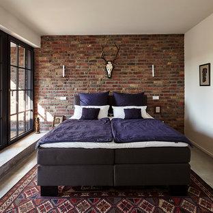 На фото: маленькая гостевая спальня в стиле лофт с разноцветными стенами, бетонным полом и серым полом с
