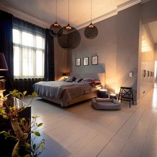 Ejemplo de dormitorio principal, grande, sin chimenea, con paredes púrpuras y suelo de madera clara