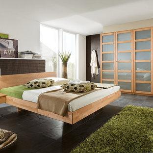 Imagen de dormitorio actual, grande, sin chimenea, con paredes blancas y suelo de pizarra
