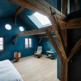 Großes Uriges Hauptschlafzimmer ohne Kamin mit blauer Wandfarbe, hellem Holzboden und beigem Boden in München