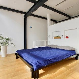 Ejemplo de dormitorio tipo loft, minimalista, grande, con paredes blancas, suelo de madera clara y suelo amarillo