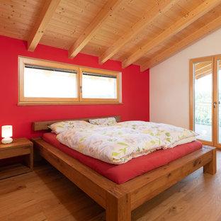 Ejemplo de dormitorio principal, actual, grande, sin chimenea, con paredes rojas, suelo de madera en tonos medios y suelo marrón