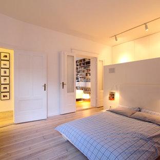 Réalisation d'une grand chambre parentale nordique avec un mur blanc, un sol en bois clair et aucune cheminée.