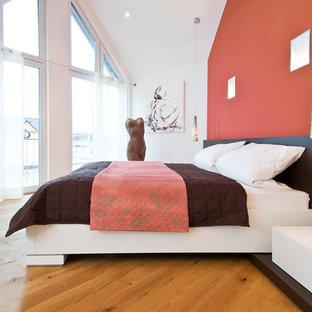Großes Modernes Hauptschlafzimmer mit roter Wandfarbe, braunem Holzboden und braunem Boden in Berlin