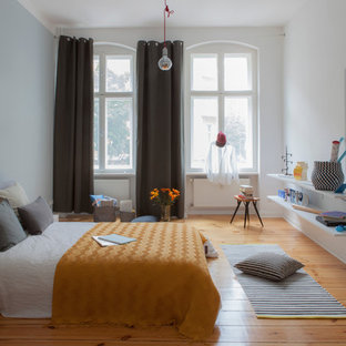 This is an example of a large scandinavian master bedroom in Berlin with white walls, medium hardwood floors, no fireplace and brown floor.
