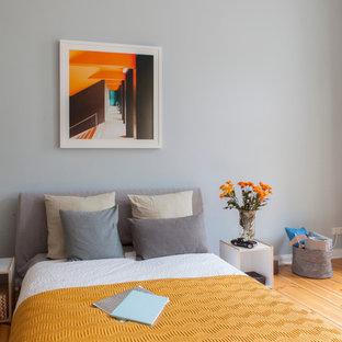 Bild på ett mellanstort industriellt sovrum, med grå väggar och mellanmörkt trägolv