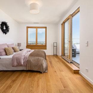 Mittelgroßes Modernes Hauptschlafzimmer ohne Kamin mit weißer Wandfarbe, braunem Holzboden und beigem Boden in München