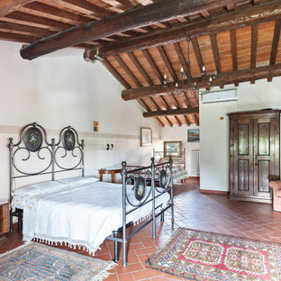 Example of a huge classic guest terra-cotta tile bedroom design in Florence with white walls