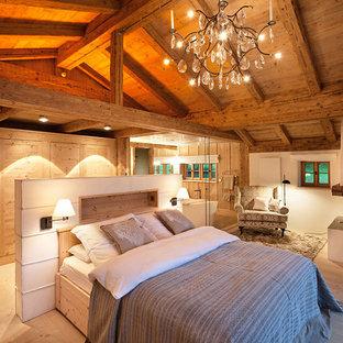 Modelo de dormitorio principal, campestre, de tamaño medio, con paredes blancas, suelo de madera clara, chimenea de esquina, marco de chimenea de yeso y suelo marrón