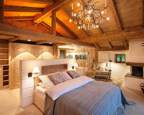 Mittelgroßes Landhaus Hauptschlafzimmer Mit Weißer Wandfarbe, Hellem  Holzboden, Eckkamin, Verputztem Kaminsims Und Braunem