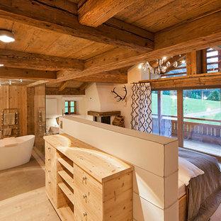 Ejemplo de dormitorio principal, rústico, de tamaño medio, con paredes blancas, suelo de madera clara, chimenea de esquina, marco de chimenea de yeso y suelo marrón