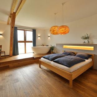 Country Schlafzimmer mit weißer Wandfarbe, braunem Holzboden und braunem Boden in München