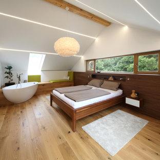 Großes Modernes Gästezimmer mit weißer Wandfarbe, hellem Holzboden und beigem Boden in München