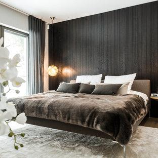 Ejemplo de dormitorio principal, minimalista, grande, sin chimenea, con paredes negras y suelo de madera en tonos medios