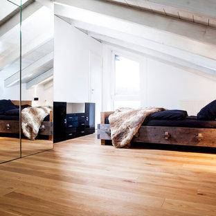 Imagen de dormitorio principal, nórdico, grande, con paredes blancas, suelo de madera clara, estufa de leña, marco de chimenea de metal y suelo marrón
