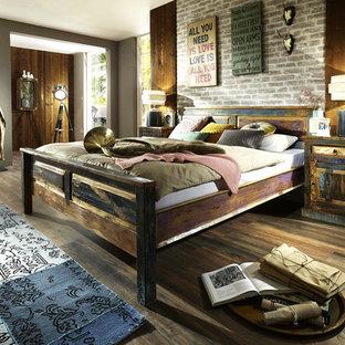 Großes Industrial Hauptschlafzimmer ohne Kamin mit bunten Wänden, dunklem Holzboden und braunem Boden in Düsseldorf