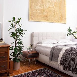 Klassisches Hauptschlafzimmer mit weißer Wandfarbe, braunem Holzboden und braunem Boden in Berlin