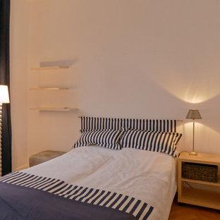 Ejemplo de dormitorio tipo loft, contemporáneo, de tamaño medio, con paredes blancas, suelo de madera en tonos medios, estufa de leña y suelo beige