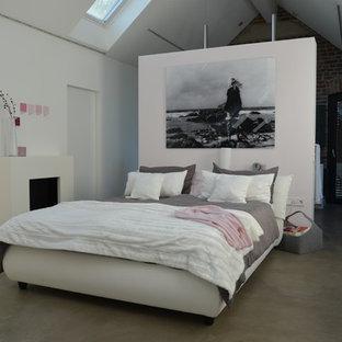 Идея дизайна: большая хозяйская спальня в современном стиле с белыми стенами, бетонным полом, стандартным камином, фасадом камина из штукатурки и серым полом