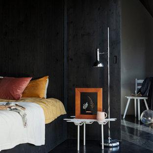 Immagine di una piccola camera degli ospiti boho chic con pareti nere, pavimento in cemento e pavimento nero