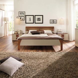 Imagen de dormitorio principal, actual, grande, sin chimenea, con paredes blancas y suelo de madera en tonos medios