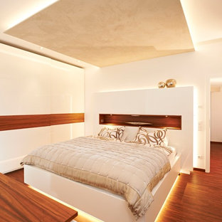 Mittelgroßes Modernes Hauptschlafzimmer ohne Kamin mit weißer Wandfarbe, braunem Holzboden und braunem Boden in Stuttgart