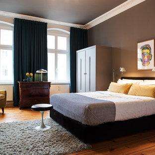 Mittelgroßes Eklektisches Hauptschlafzimmer mit grauer Wandfarbe, hellem Holzboden und braunem Boden